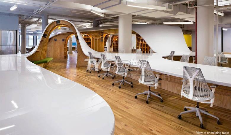 """应Barbarian Group委托,建筑师克莱夫•威尔金森(Clive Wilkinson)创造出这张""""超级工作台"""",价值超30万美元(约合人民币184万元)。桌面延展335米,中间没有任何间断。为了腾出会议场地和更多私人空间,整张桌面呈现滚动和起伏结构,桌面以下部分包括胶合板拱门、多个小房间以及储物空间,让整张桌子看起来好像冲浪板。超级桌采用低成本的中纤板与夹板由工厂加工再运至现场安装,白色台面搭配赫曼米勒(Herman Miller)座椅成为构建空间的主要装饰元素。"""